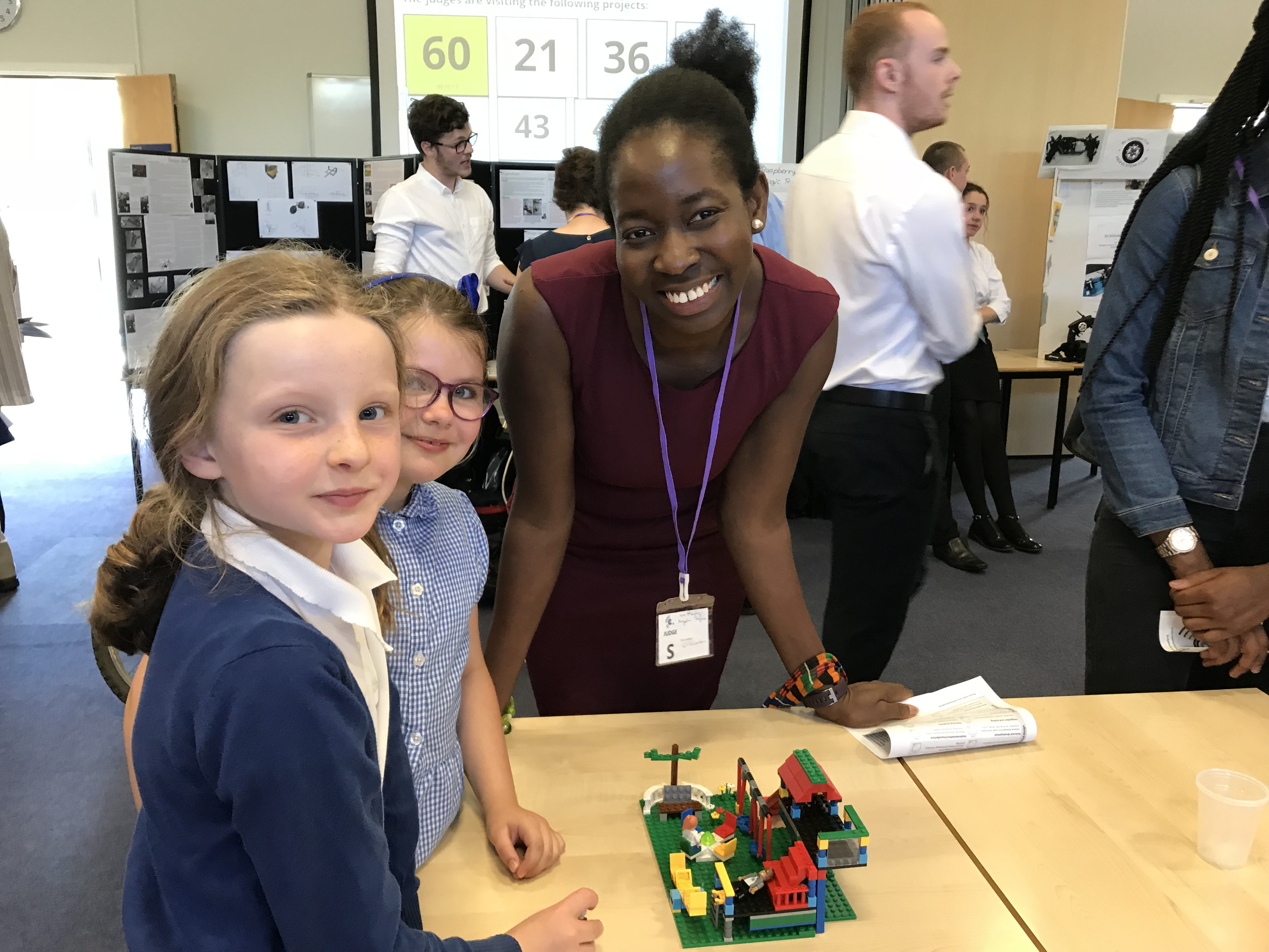 Competition judge Hephzi Angela Tagoe speaks with primary school pupils Erika and Rose